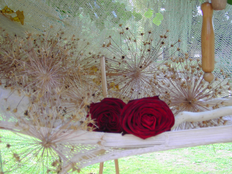 Bild von einer Ikebana-Installation: in einer weißen Hängematte liegen sternförmige Blütenstände und zwei rote Rosenblüten